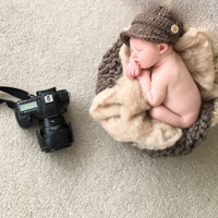 Newborn boy naked in a basket with knitted brown hat in Gainesville newborn photographer studio