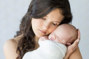Gainesville newborn photographer beautiful new mom cradling her newborn girl close to her face both of them with eyes closed