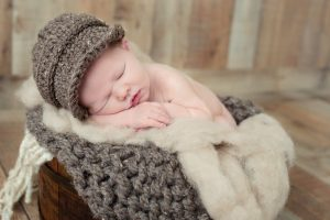Newborn boy with brown knitted hat and chunky knit blanket in bucket of wool fluff