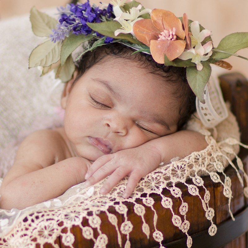 Newborn girl in brown bucket wiht lace and flowers