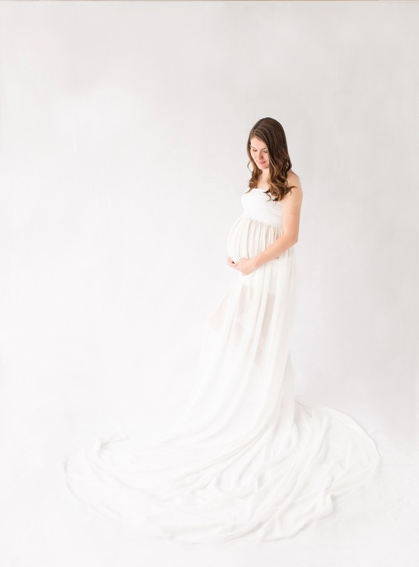 Expectant mom in white gown posed against white backdrop looking at beautiful baby bump Gainesville Florida Maternity photos
