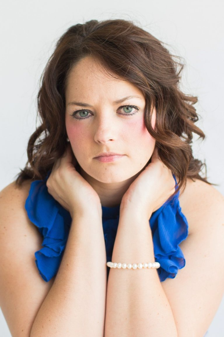 Beautiful woman big blue eyes brown curly hair hands cupped around chin celebrates beauty with glamor photos royal blue sleeveless ruffle dress Gainesville Florida Womens Portraiture