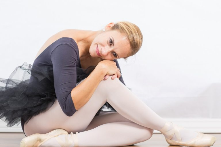 Beautiful woman big brown eyes smiling celebrates beauty posed seated legs crossed with dance black tutu pink pointe shoes Gainesville Florida Womens Portraiture