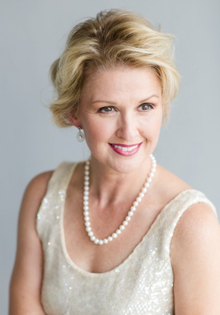 Gorgeous blond middle aged woman big brown eyes smiling stylized professional head shot celebrates beauty glamor pose white sequin blouse pearls Gainesville Florida Womens Portraiture