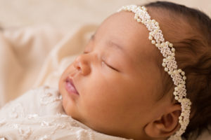 Newborn girl with pearls head tie and flowers on lace