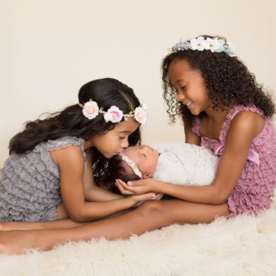 Joyful sisters loving newborn sister in Gainesville Florida