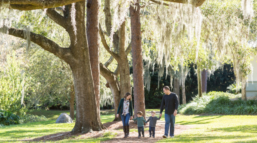 Family walking at park with two year old twin boys