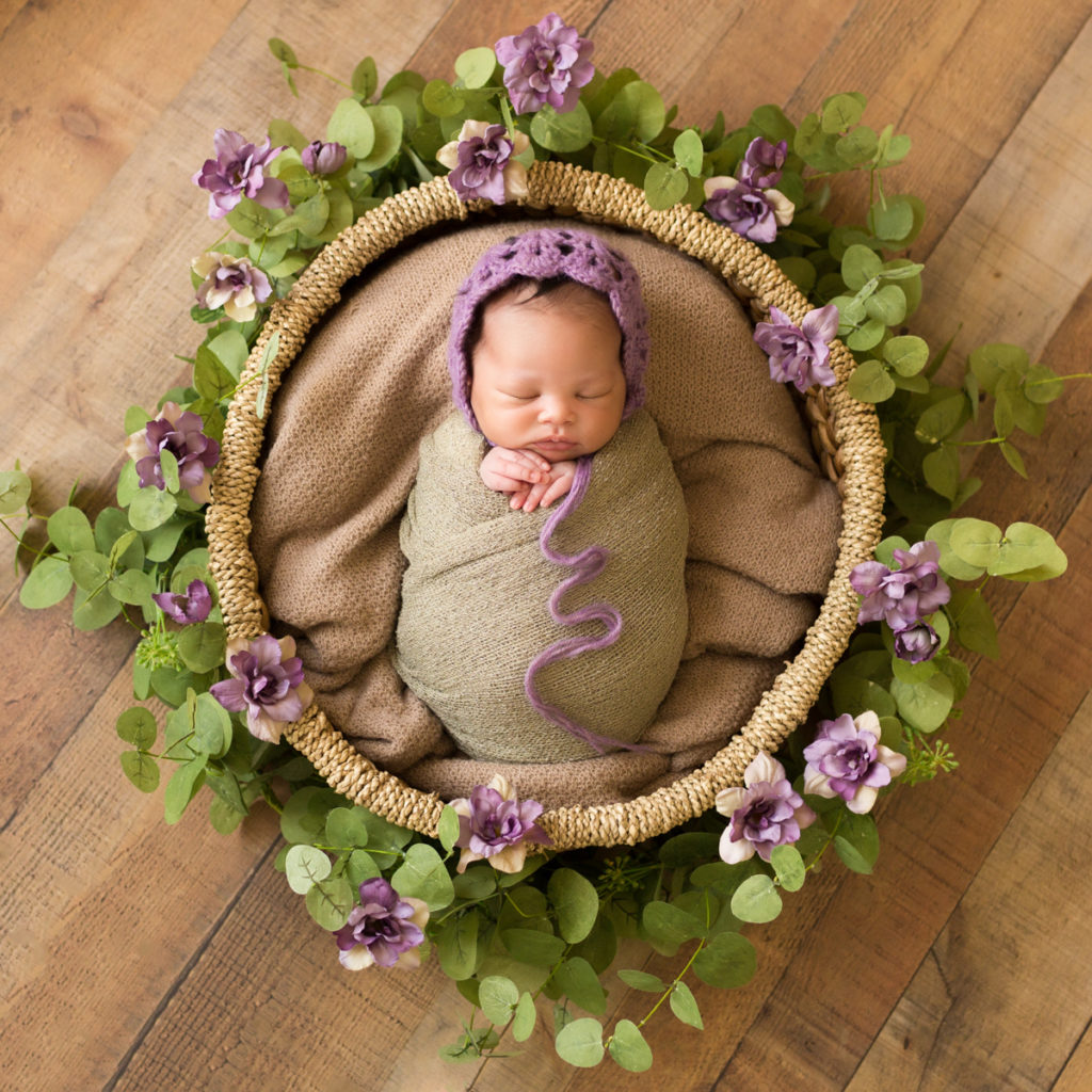 Babygirl with purple bonnet and purple flower basket on wood in Newborn Photosession