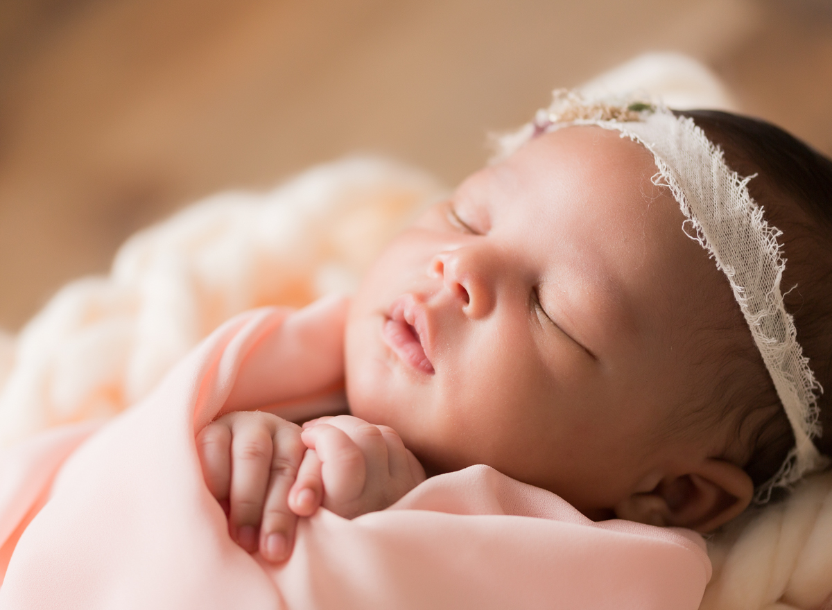 Babygirl face and fingers in peach on chunky knit blanket in Newborn Photosession