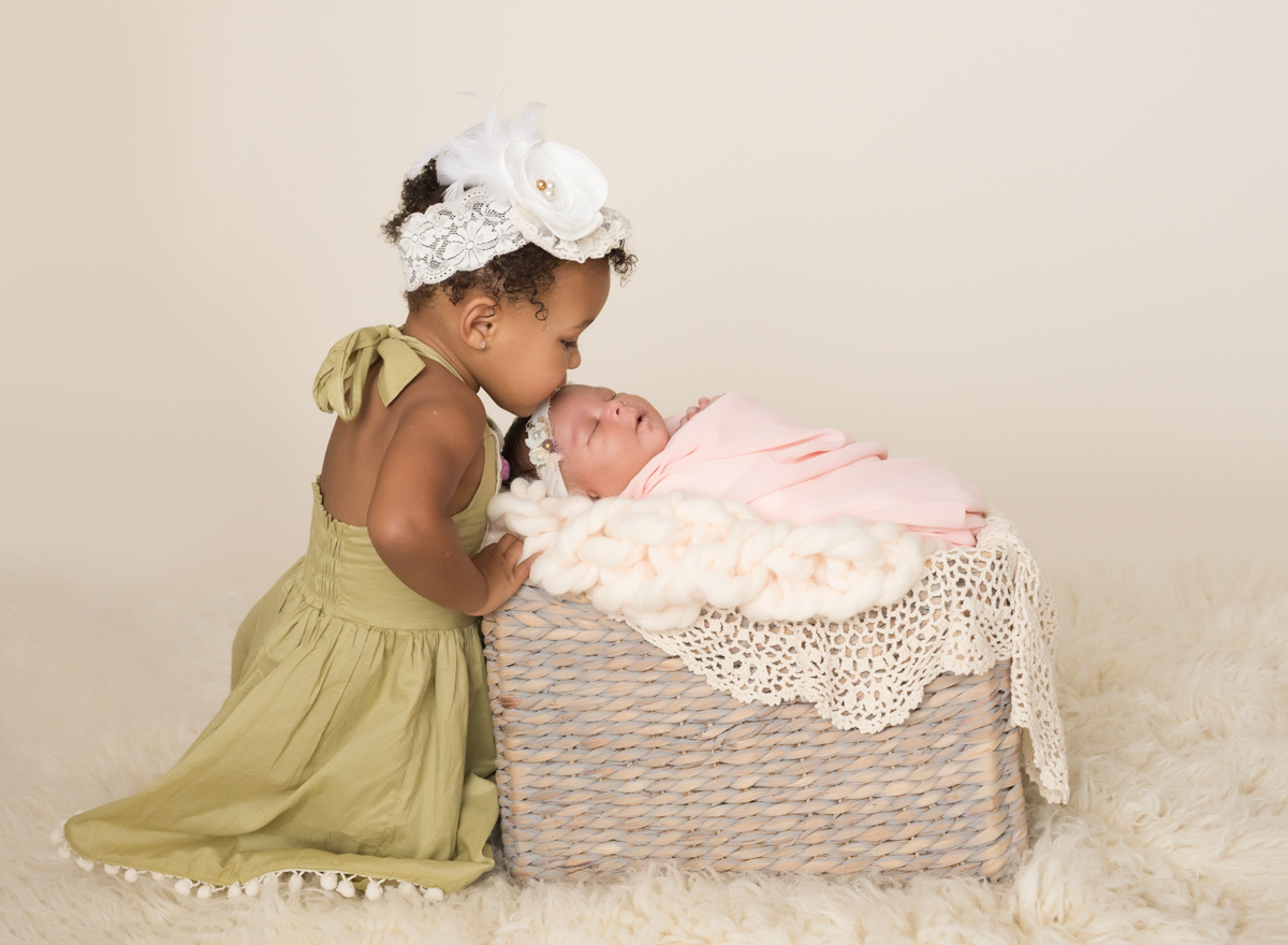 Babygirl with happy sister in Newborn Photosession with basket chunky knit blanket and lace