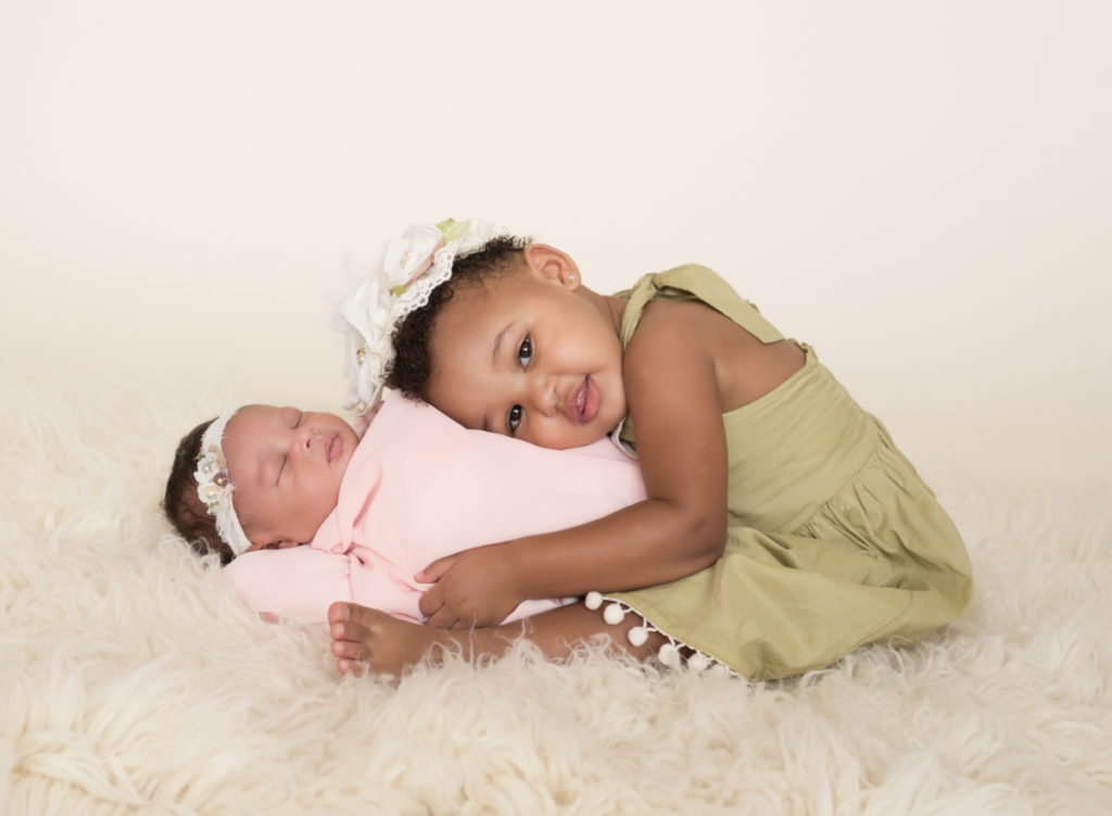 Babygirl with happy sister in newborn photosession on cream fur