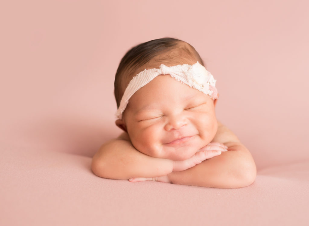 Babygirl grins propped up on arms in newborn photosession on soft pink baby blanket 2