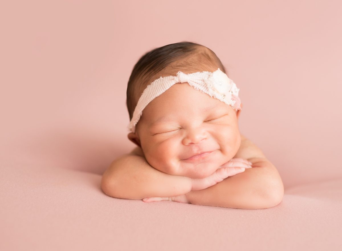 Babygirl grins propped up on arms in Newborn Photosession on Soft Pink Baby Blanket-2