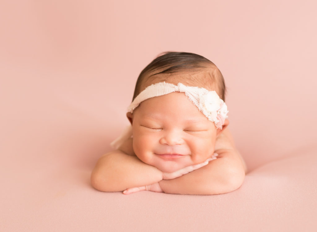 Babygirl grins propped up on arms in newborn photosession on soft pink baby blanket