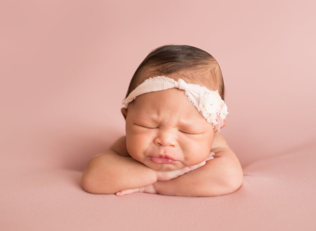 Babygirl funny face propped up on arms in Newborn Photosession on Soft Pink Baby Blanket