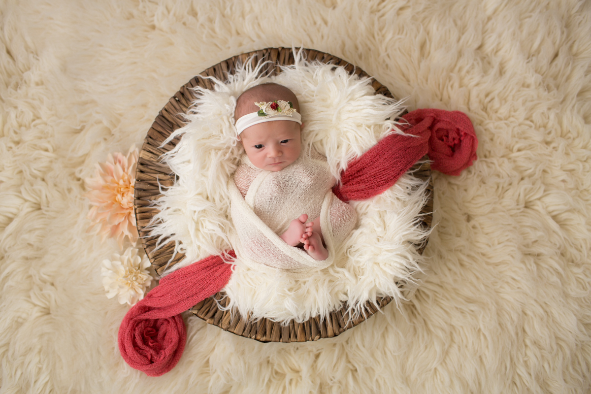 Baby girl Charleigh in round basket with cream fur and peach flowers in Gainesville Florida
