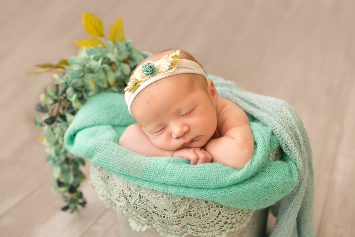 Baby girl Charleigh all wrapped up in bucket with aqua lace and flowers in Gaineville Florida