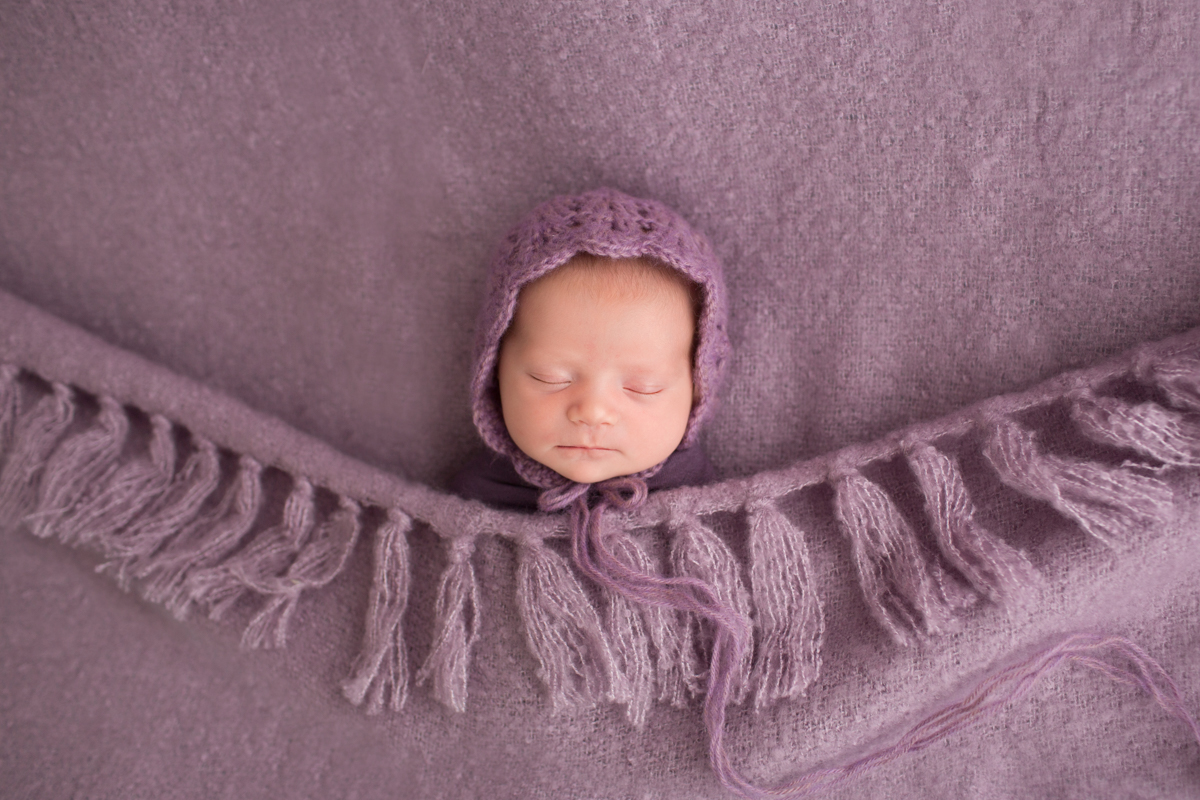 Baby girl Charleigh asleep tucked in purple bedspread and bonnet in Gainesville Florida