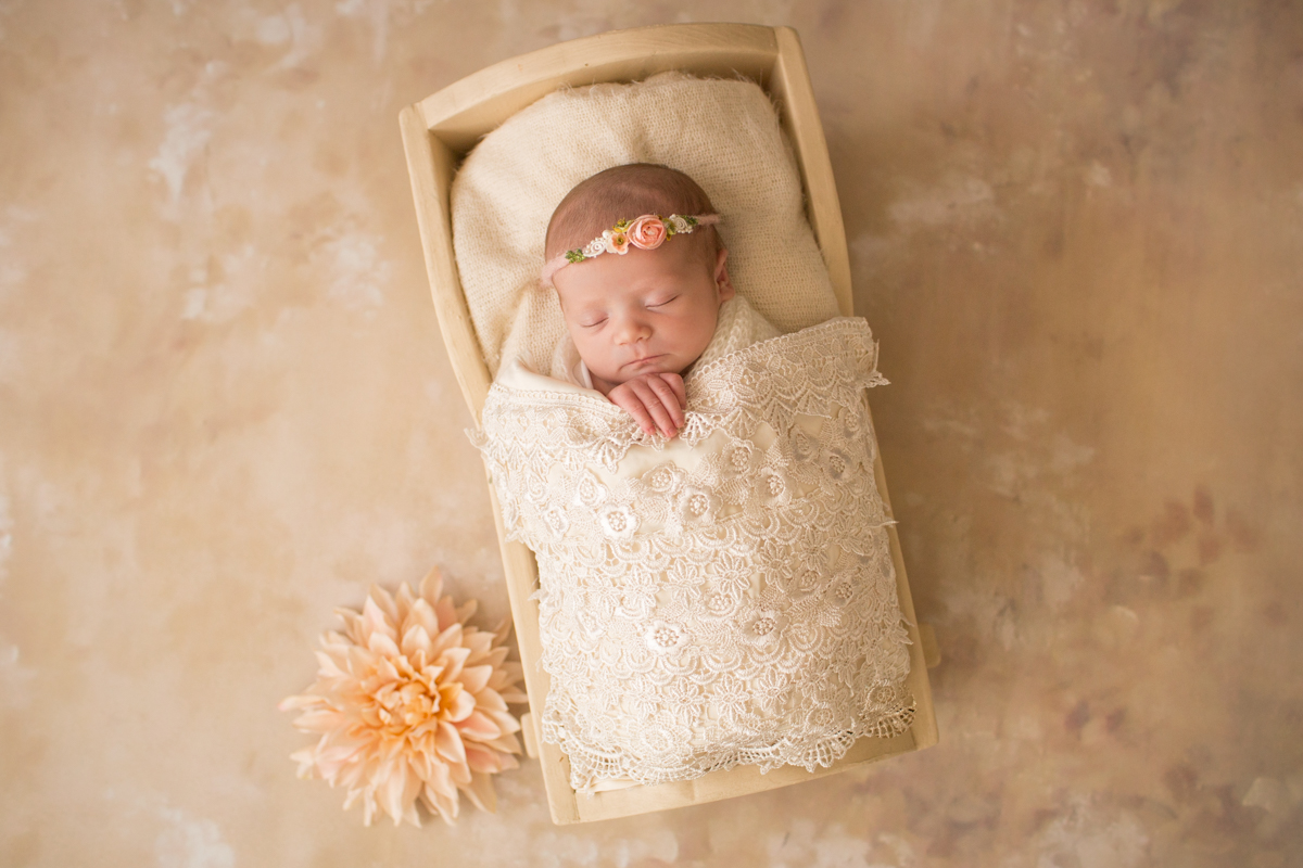 Baby girl Charleigh in cradle with lace and flowers and floral headband in Gainesville Florida