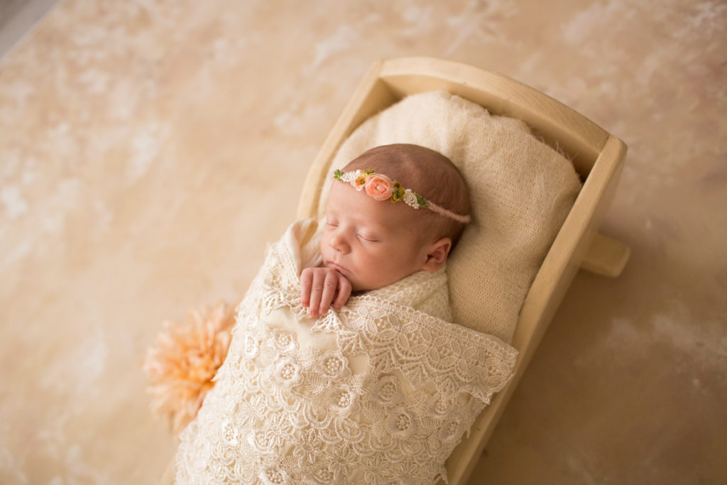 Baby girl Charleigh in cradle with lace and flowers in Gainesville Florida