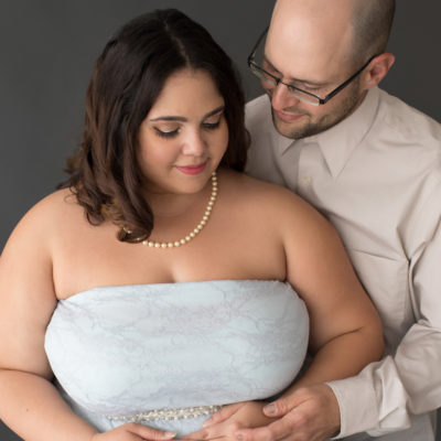 Maternity Indoor Photos of Pregnant woman in Blue Lace gown and Pearls with husband gazing at her in Alachua Florida