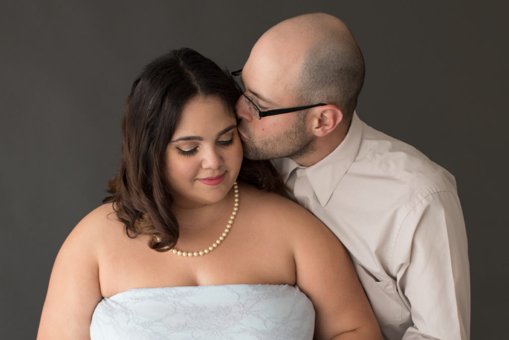 Maternity Indoor Photos of Pregnant Adelis in Blue Lace gown and Pearls getting kiss from husband in Alachua Florida
