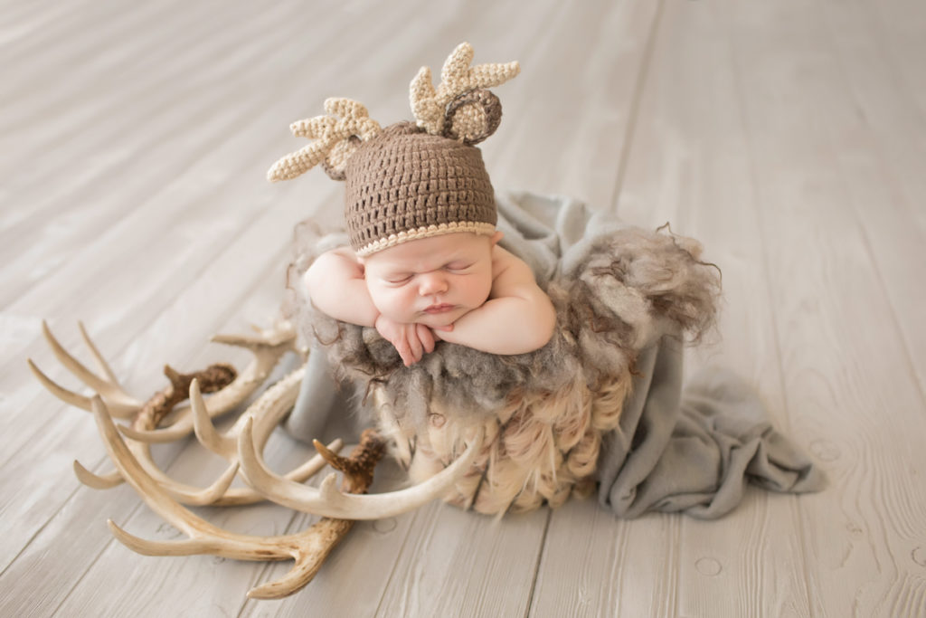 Baby newborn boy in bucket with fur antlers and bonnet in Gainesville Florida