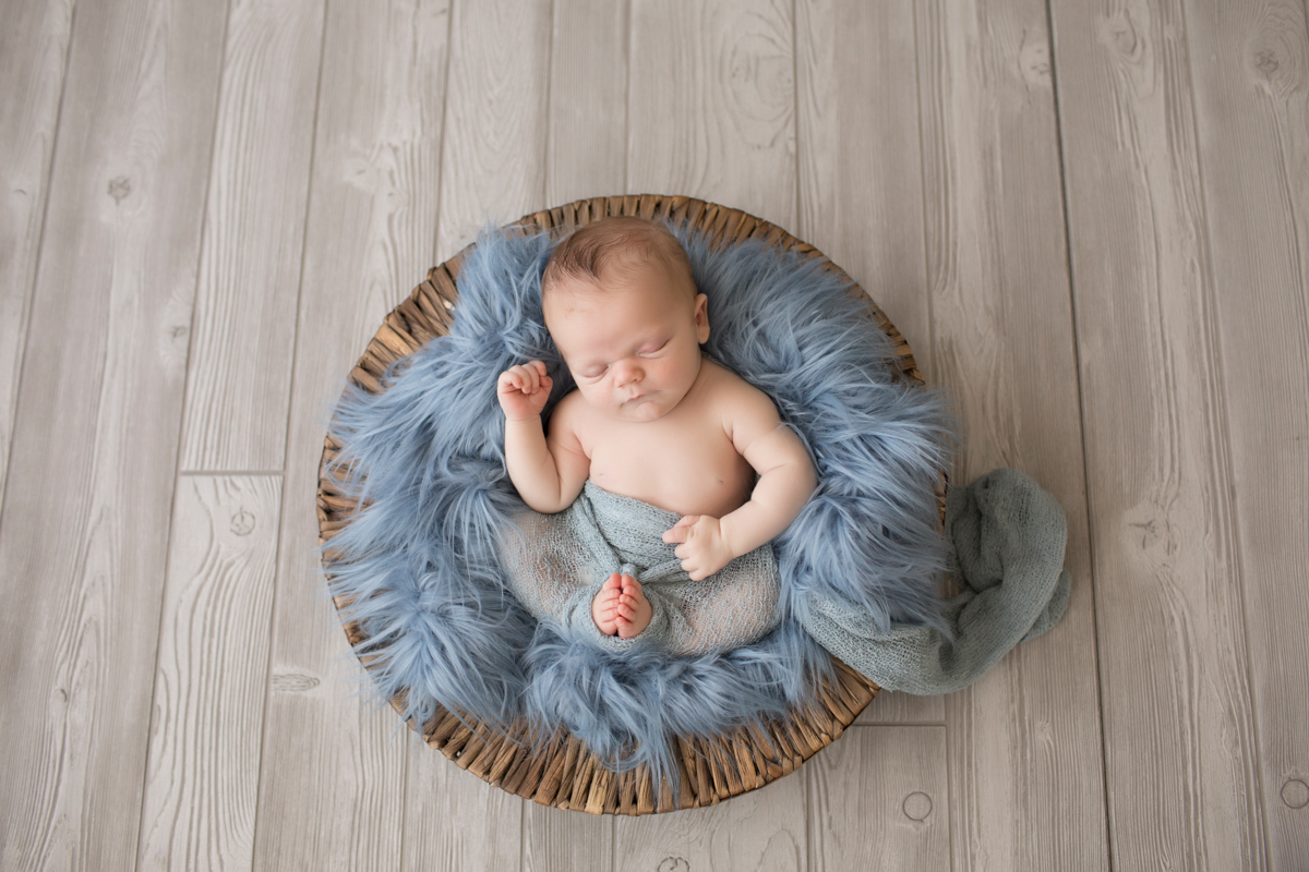 Baby newborn boy in basket with blue fur and wrap in Gainesville Florida