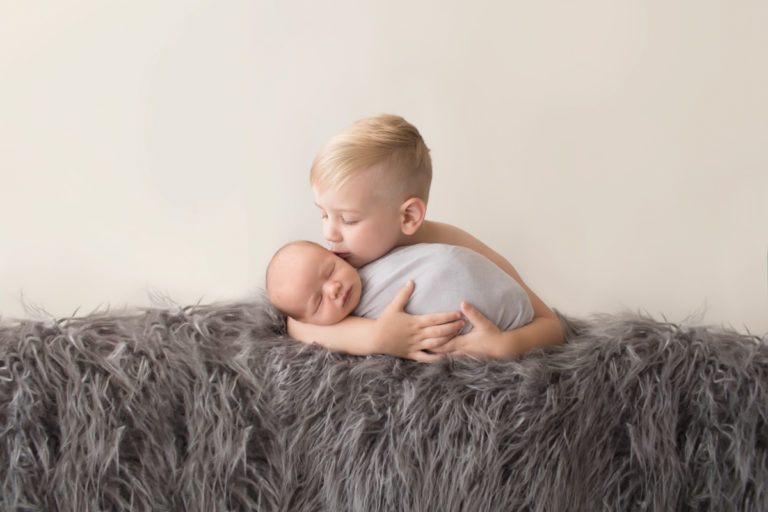 Toddler cuddling and kissing baby brother newborn wrapped in grey blanket on grey rug in Gainesville Florida