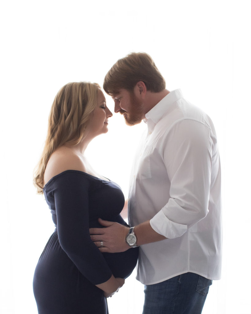 Maternity mom in navy gown with dad in romantic embrace against backlit window