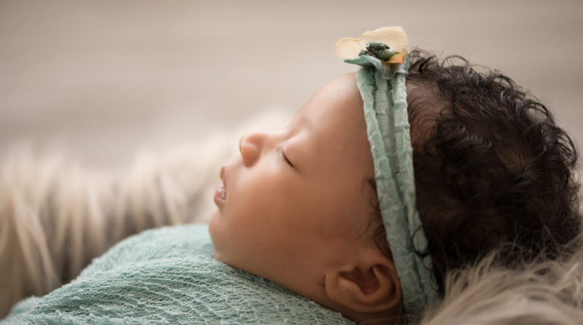 Newborn Girl Ayana close up wrapped in aqua and teal wrap and headband on grey fur with soft light coming from behind her profile face features photos Gainesville FLorida