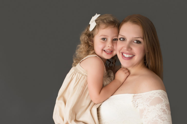 Morgan and daughter Sydney close up beautiful faces dressed in coordinating gowns for maternity photos in Gainesville FLorida