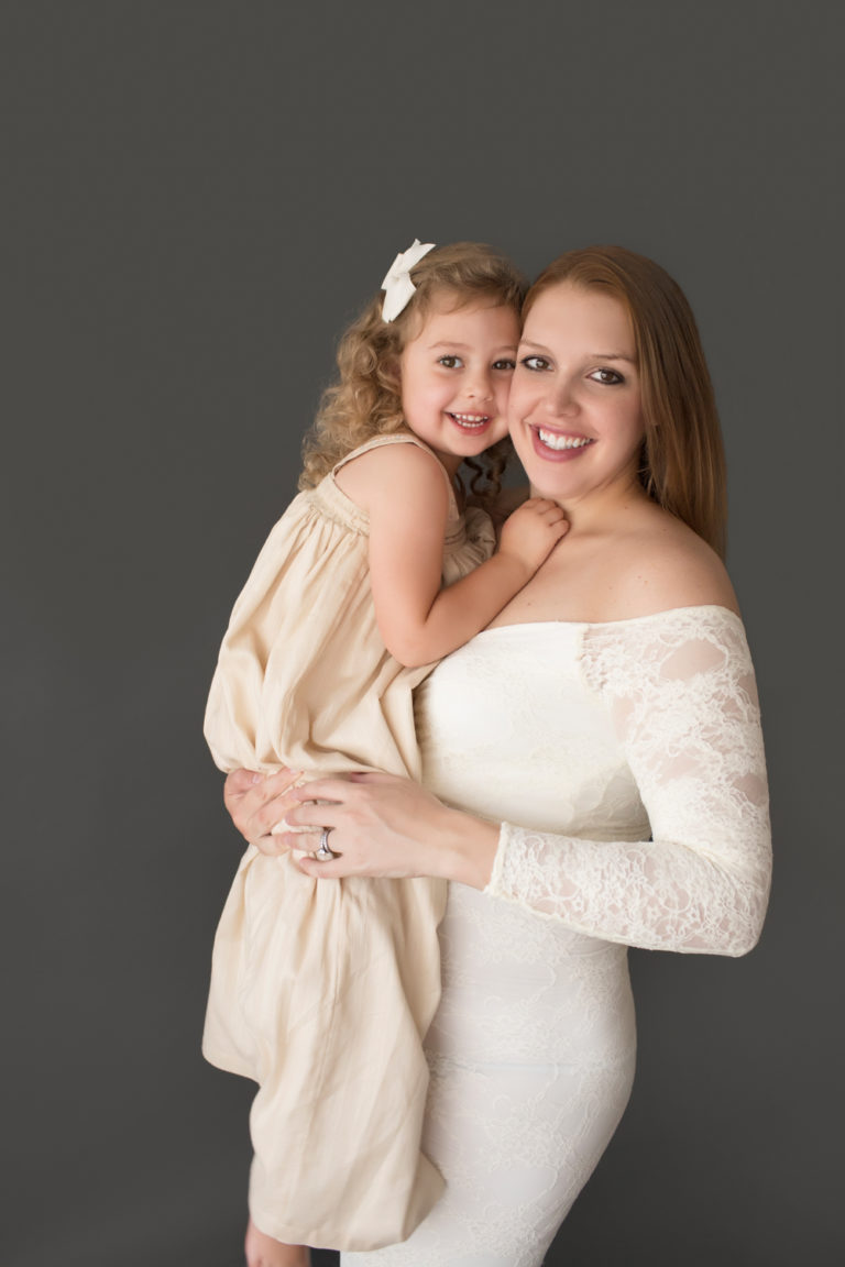 Morgan and daughter Sydney cuddling standing pose dressed in coordinating gowns for maternity photos in Gainesville FLorida