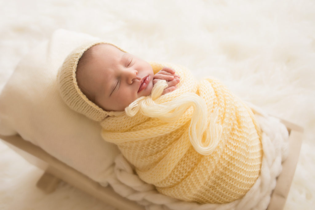Newborn baby girl Bailey lying in cream bed wrapped in buttercream yellow knit blanket with matching bonnet Gainesville FL Andrea Sollenberger Photography