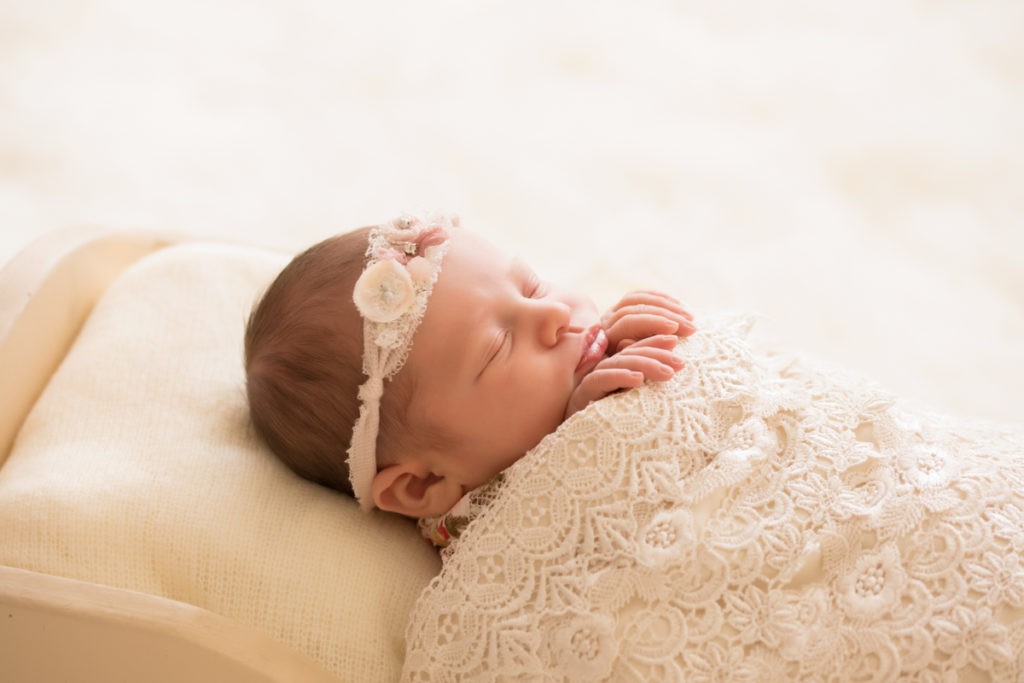 Newborn baby girl Bailey profile lying in cream bed wrapped in ivory lace with baby fingers wrapped on lace blanket lace headtie Gainesville FL Andrea Sollenberger Photography