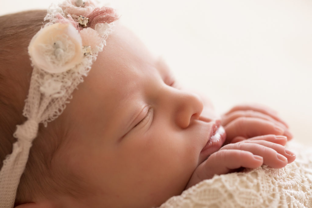 Newborn baby girl Bailey close up profile wrapped in ivory lace with baby fingers wrapped on lace blanket lave headtie Gainesville FL Andrea Sollenberger Photography