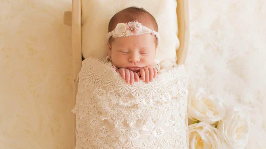 Newborn baby girl Bailey lying in cream bed wrapped in ivory lace with baby fingers wrapped on lace blanket and cream roses Gainesville FL Andrea Sollenberger Photography