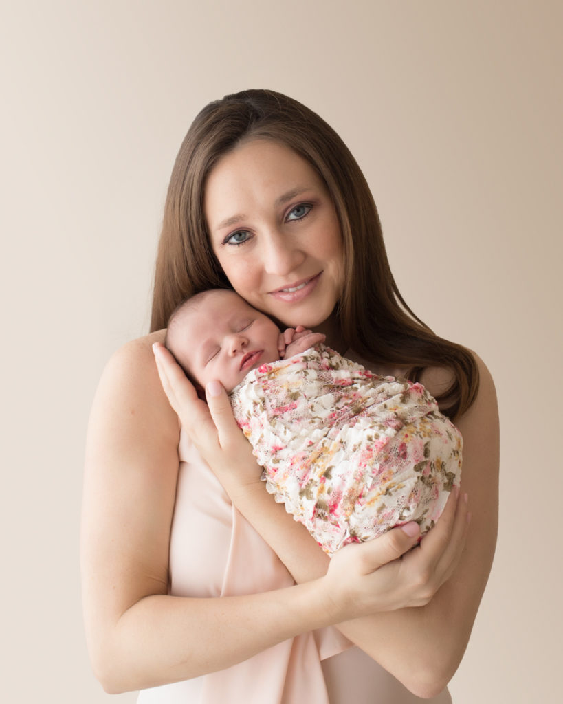 Gorgeous mom portrait smiling looking at camera cuddling newborn baby girl Bailey in pink floral wrap Gainesville FL Andrea Sollenberger Photography
