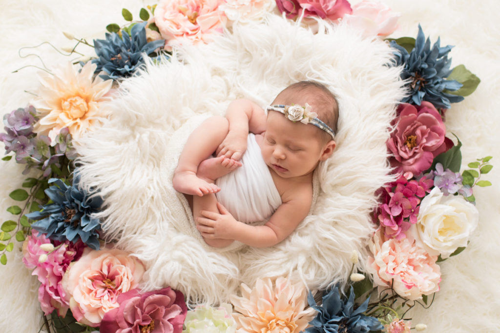 Newborn baby Bailey lying on back on white fur with floral headtie encircled with floral wreath Gainesville FL Andrea Sollenberger Photography