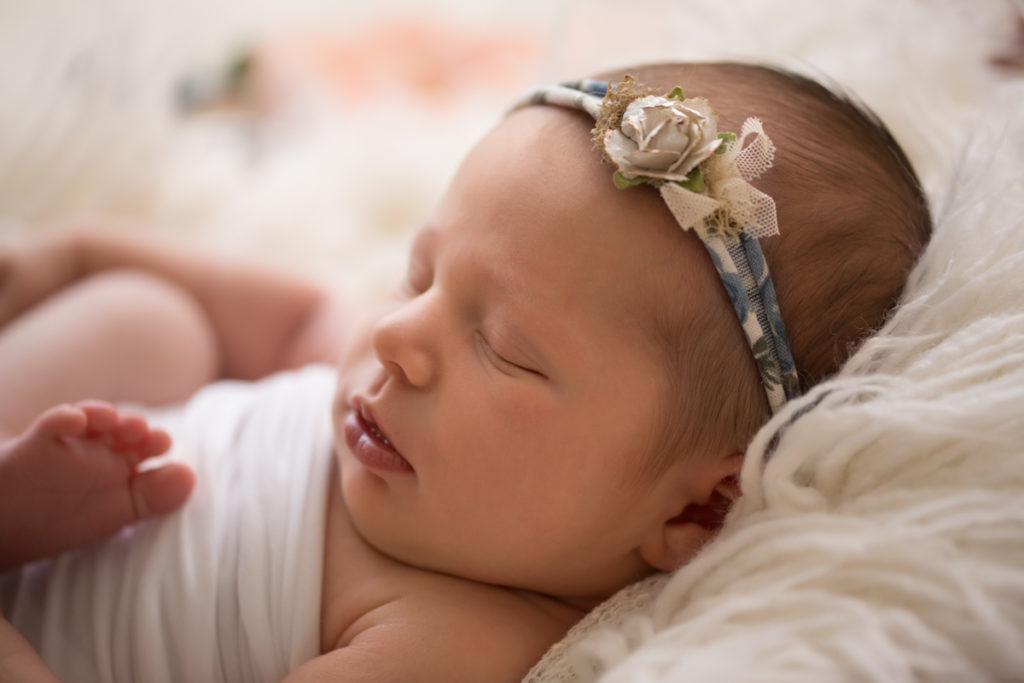Newborn baby Bailey on white fur with floral headtie soft light Gainesville FL Andrea Sollenberger Photography