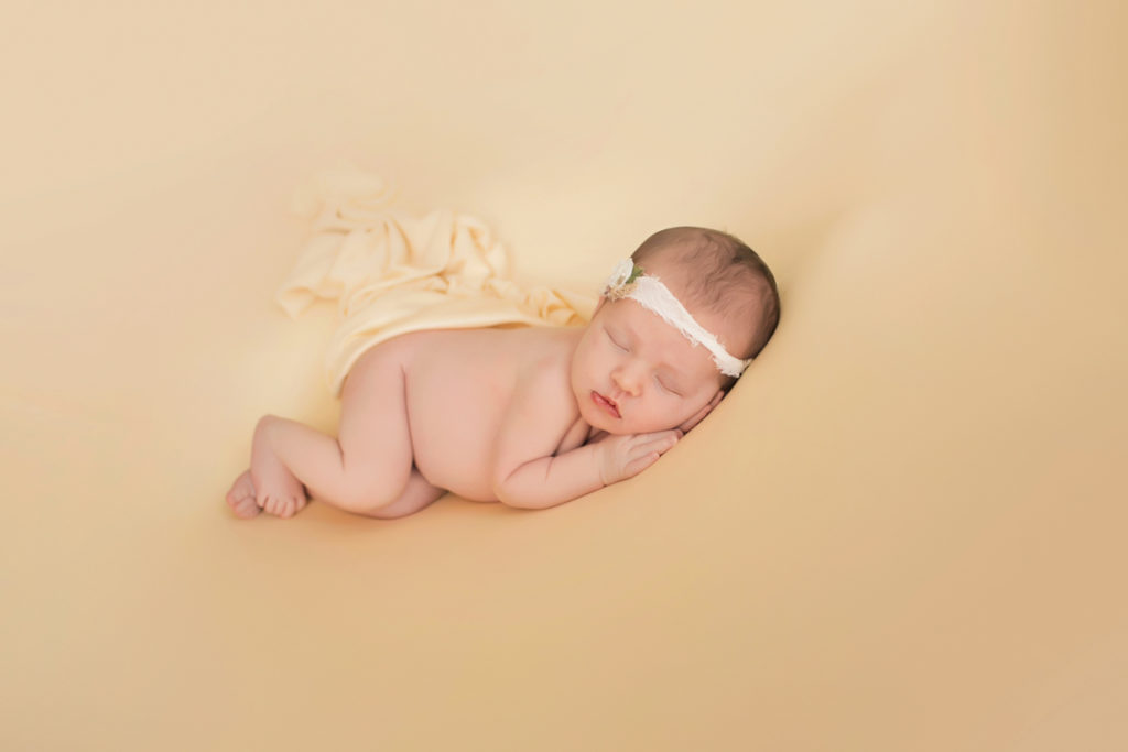 Newborn baby girl Bailey lying on side on buttercream blanket with lace headtie Gainesville FL Andrea Sollenberger Photography