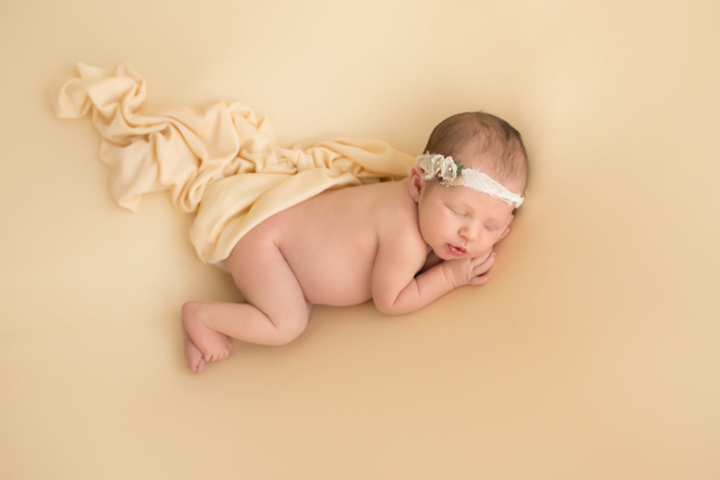 Newborn baby girl Bailey lying on side on buttercream blanket with lace headtie camera from above Gainesville FL Andrea Sollenberger Photography