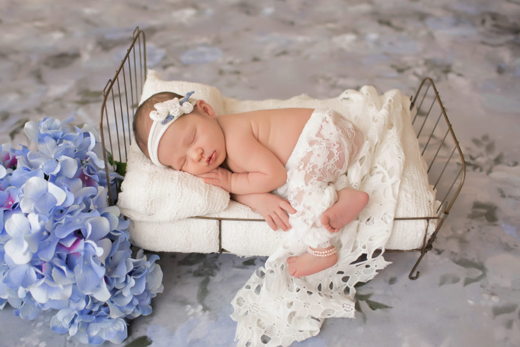Newborn baby girl Bailey lying on side on metal bed white blanket white lace blue flowers pearls and floral white headtie Gainesville FL Andrea Sollenberger Photography