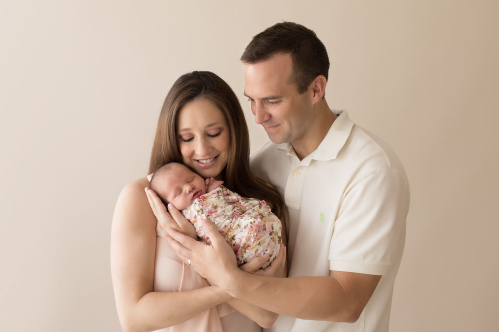 Gorgeous mom handsome dad neutral color portrait smiling looking down and cuddling newborn baby girl Bailey in pink floral wrap Gainesville FL Andrea Sollenberger Photography