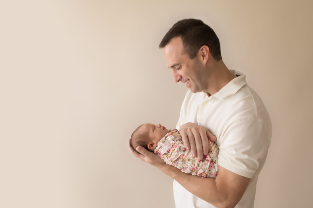 Handsome dad neutral color profile portrait smiling looking down and cuddling newborn baby girl Bailey in pink floral wrap Gainesville FL Andrea Sollenberger Photography