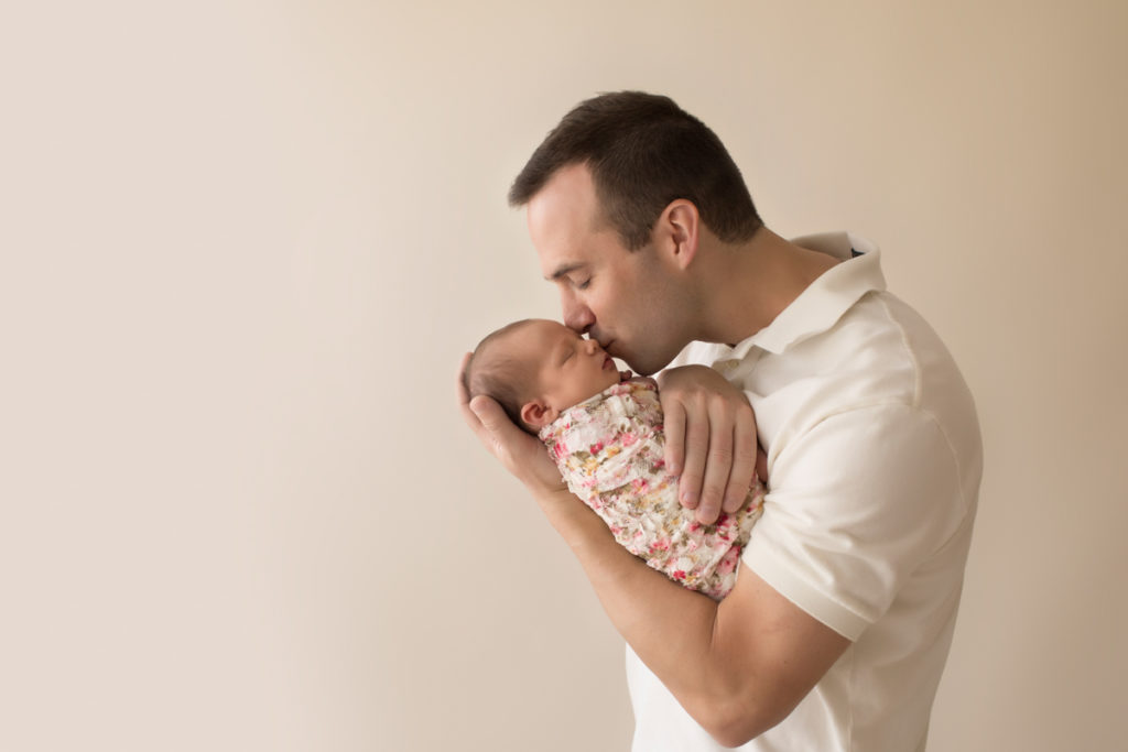 Handsome dad neutral color portrait kissing and cuddling newborn baby girl Bailey in pink floral wrap Gainesville FL Andrea Sollenberger Photography