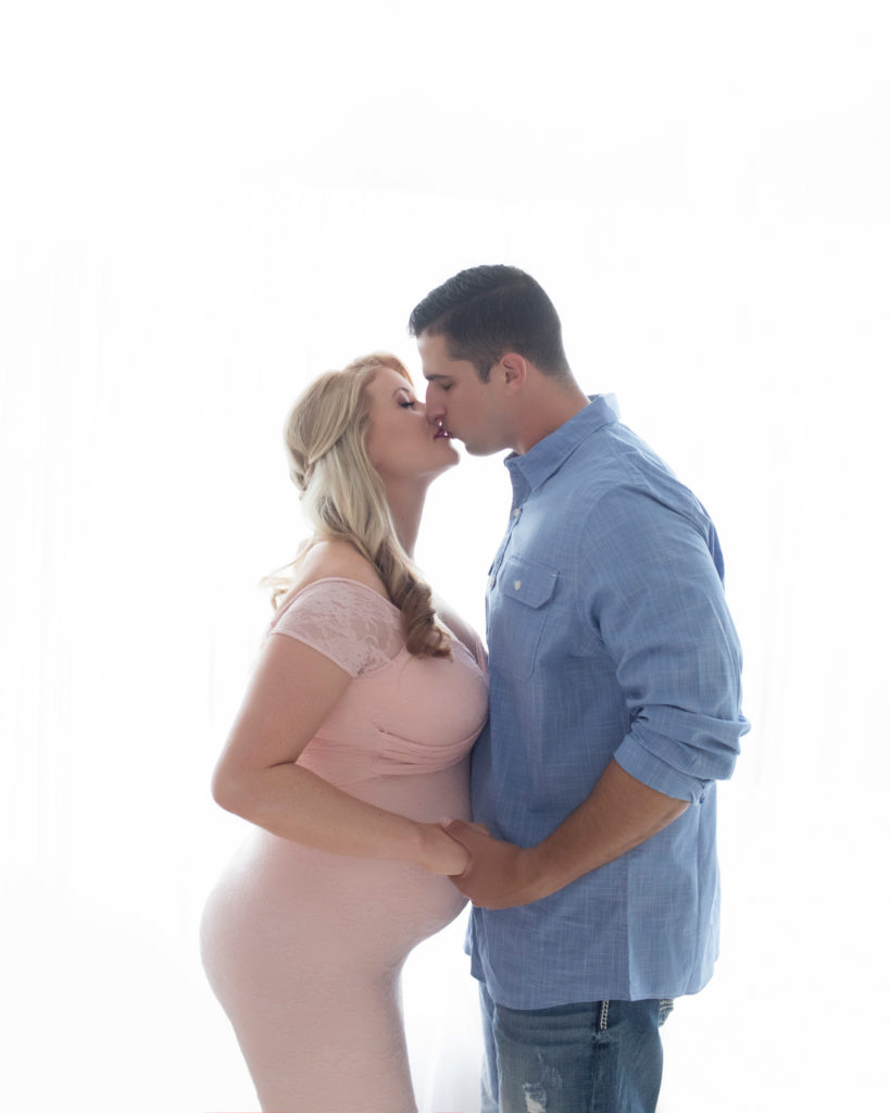 Maternity photos Christina mom face to face with her man Jamie kissing against backlight profile beautiful belly bump wearing mermaid style full length pale pink lace gown Gainesville Florida