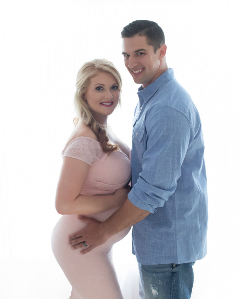 Maternity photos Christina mom with husband Jamie smiling at camera against backlight profile beautiful belly bump wearing mermaid style full length pale pink lace gown Gainesville Florida