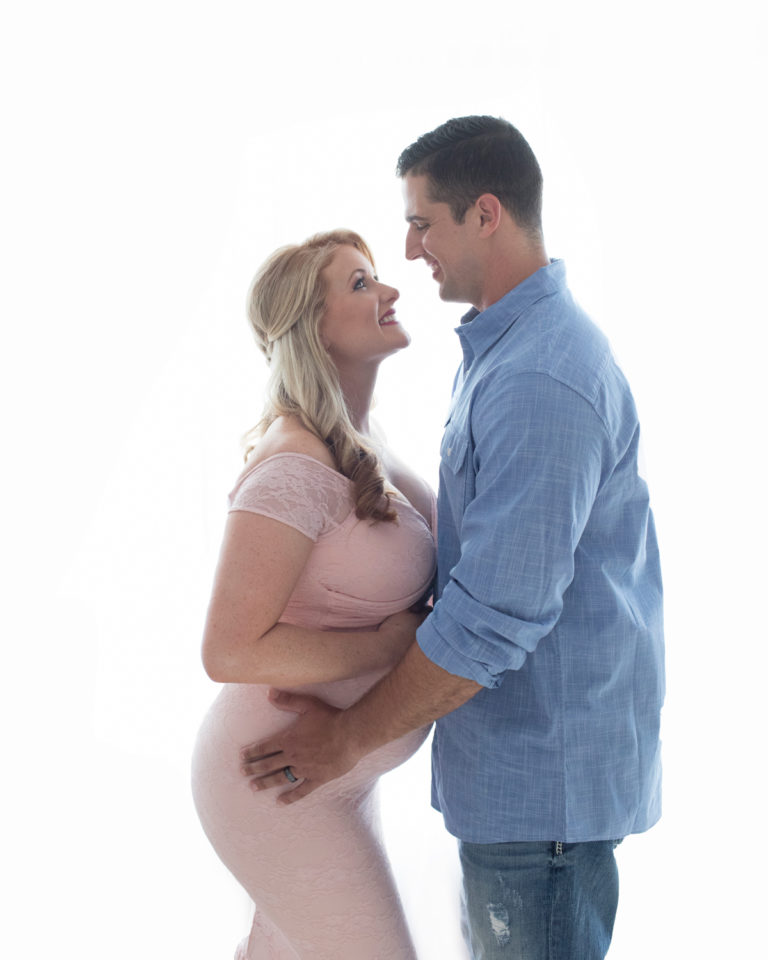 Maternity photos Christina mom face to face with husband Jamie against backlight looking down profile beautiful belly bump wearing mermaid style full length pale pink lace gown Maternity Baby Photographer FL Gainesville