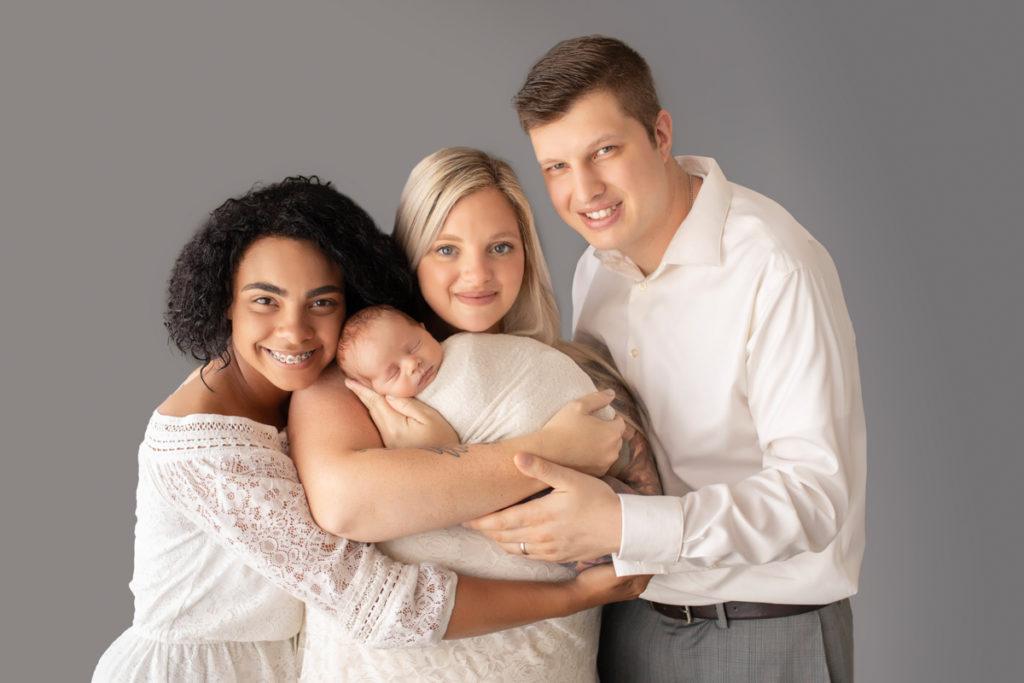 Mom dad big sister looking up smiling cuddling newborn baby Rowan Gainesvile Florida Photos